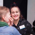 Kuvassa Annika Lius hymyilee keskustellessaan toisen henkilön kanssa.