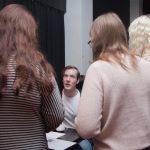 Kuvassa Antti Rädyn ympärillä seisoo kolme henkilöä kuuntelemassa, kun Räty puhuu.