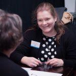 Kuvassa Johanna Albert hymyilee keskustellessaan toisen henkilön kanssa.