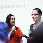 Kuvassa kaksi tummahiuksista naista mikrofonit kädessään.