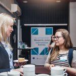 Kuvassa kaksi naista keskustelevat, kädessään kakkulautaset ja edessään kahvikuppeja.