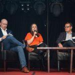 Kuvassa kolme panelistia istuu vierekkäin, keskimmäinen puhuu mikrofoniin.