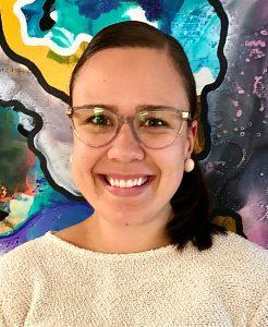 Kuvassa tummahiuksinen nainen (Hanna Puro) hymyilee leveästi.