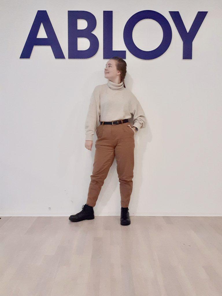 Kuvassa harjoittelija Laura Väänänen seisoo ABLOY-tekstin alla.