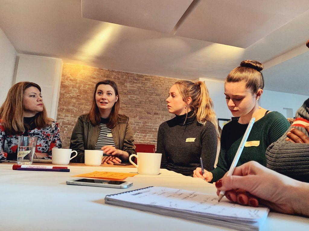 Kuvassa Vilja Byström ja kolme muuta naista pöydän ääressä, kahvikupit edessään.