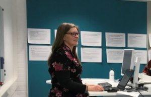Kuvassa pitkähiuksinen nainen puhuu hymyillen. Taustalla näkyy tietokone ja seinä, johon on kiinnitetty papereita.