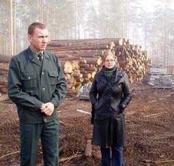 Kuvassa vihreään uniformuun sonnustautunut mies ja mustaan nahkatakkiin sonnustautunut nuori nainen (Sonja Kortelainen) seisovat tukkipinon edessä.