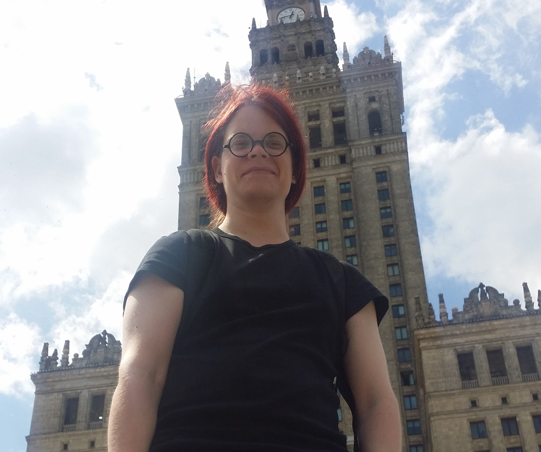 Person in front of a high, old building.