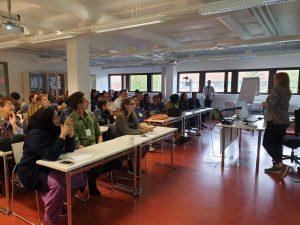 Ihmisiä istumassa luokkahuoneessa.