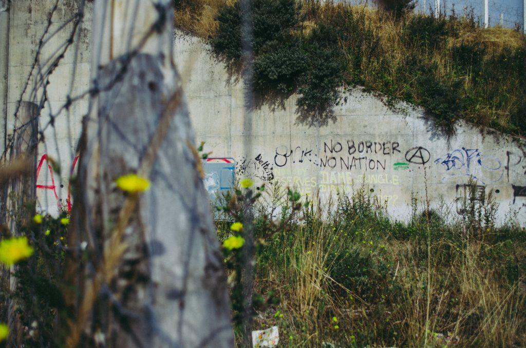 Graffiteilla koristeltu sementtiseinä heinittyneessä ympäristössä.