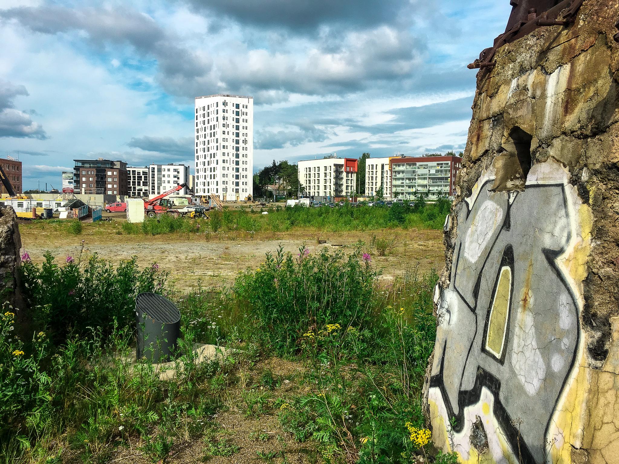 Graffitien täyttämä kiviseinä, niitty ja taustalla näkyvä kaupunki.