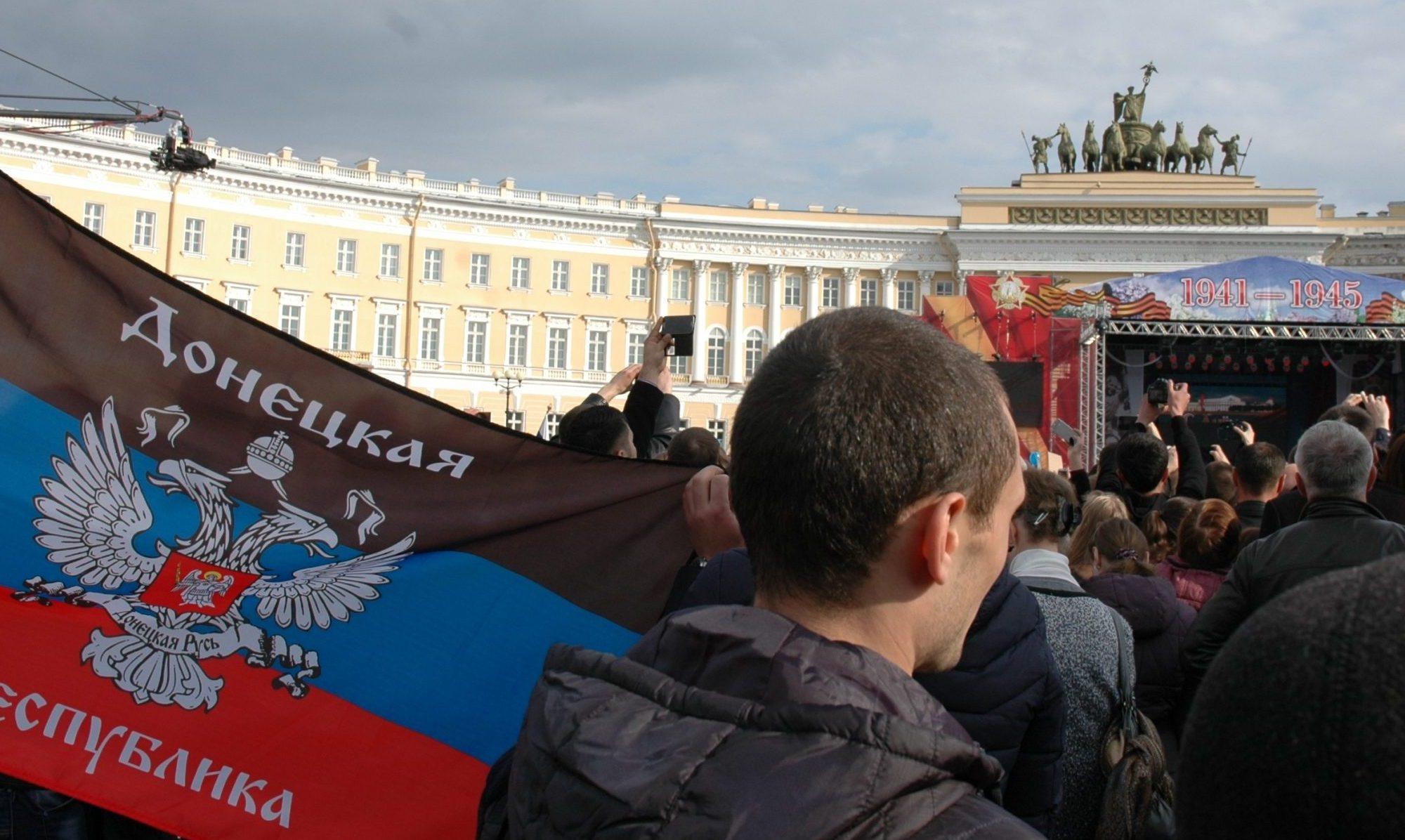 Lippua pitelevä mies ihmisten täyttämällä aukiolla.