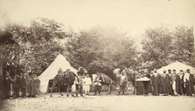 Old photo, behind a tent and in front of it camels and groups of people.