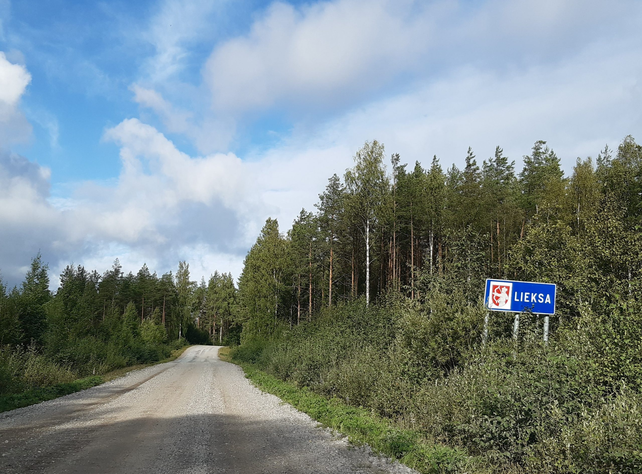 Image of a dirt road and a road sign that reads 'Lieksa'
