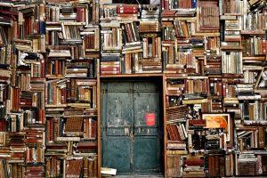 Koristekuva. Kirjojen täyttämä seinä, jonka keskellä ovi.