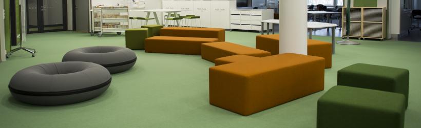 Kuvassa oransseja, vihreitä ja harmaita istuimia yhteistilassa