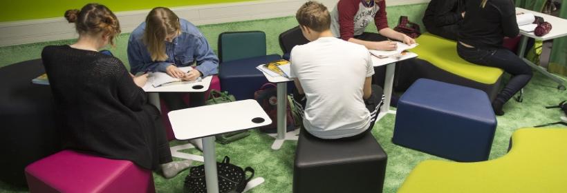 Kuvassa oppilaita työskentelemässä koulutehtävien pärissä, tilassa värikkäitä istuimia ja vihreät seinät