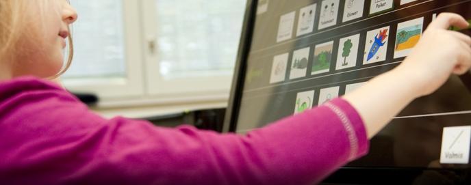 Tyttö valitsee tietokoneelta AAC-kuvaa