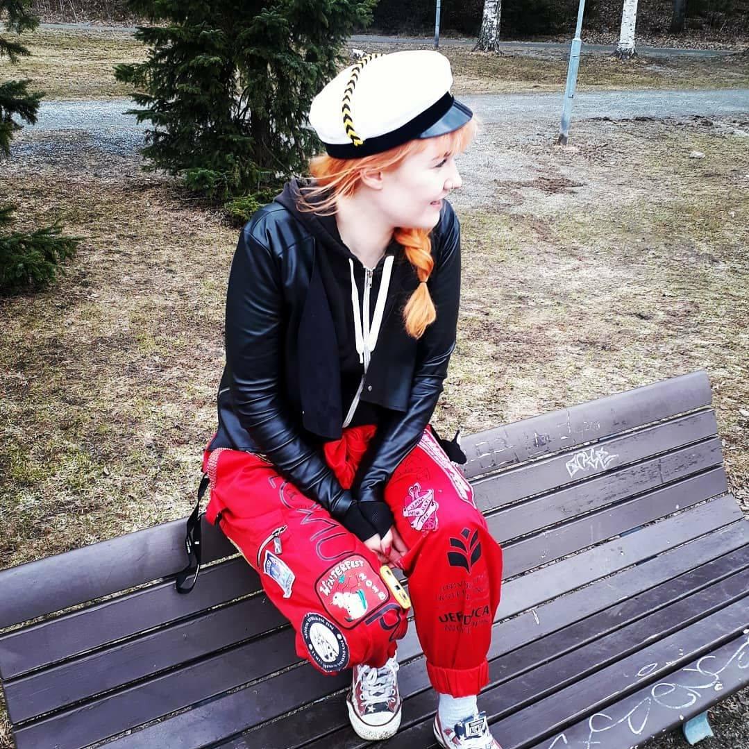 Lähettiläs-Maria istuu ylioppilaslakissaan ja haalareisa puiston penkillä Vappuna.
