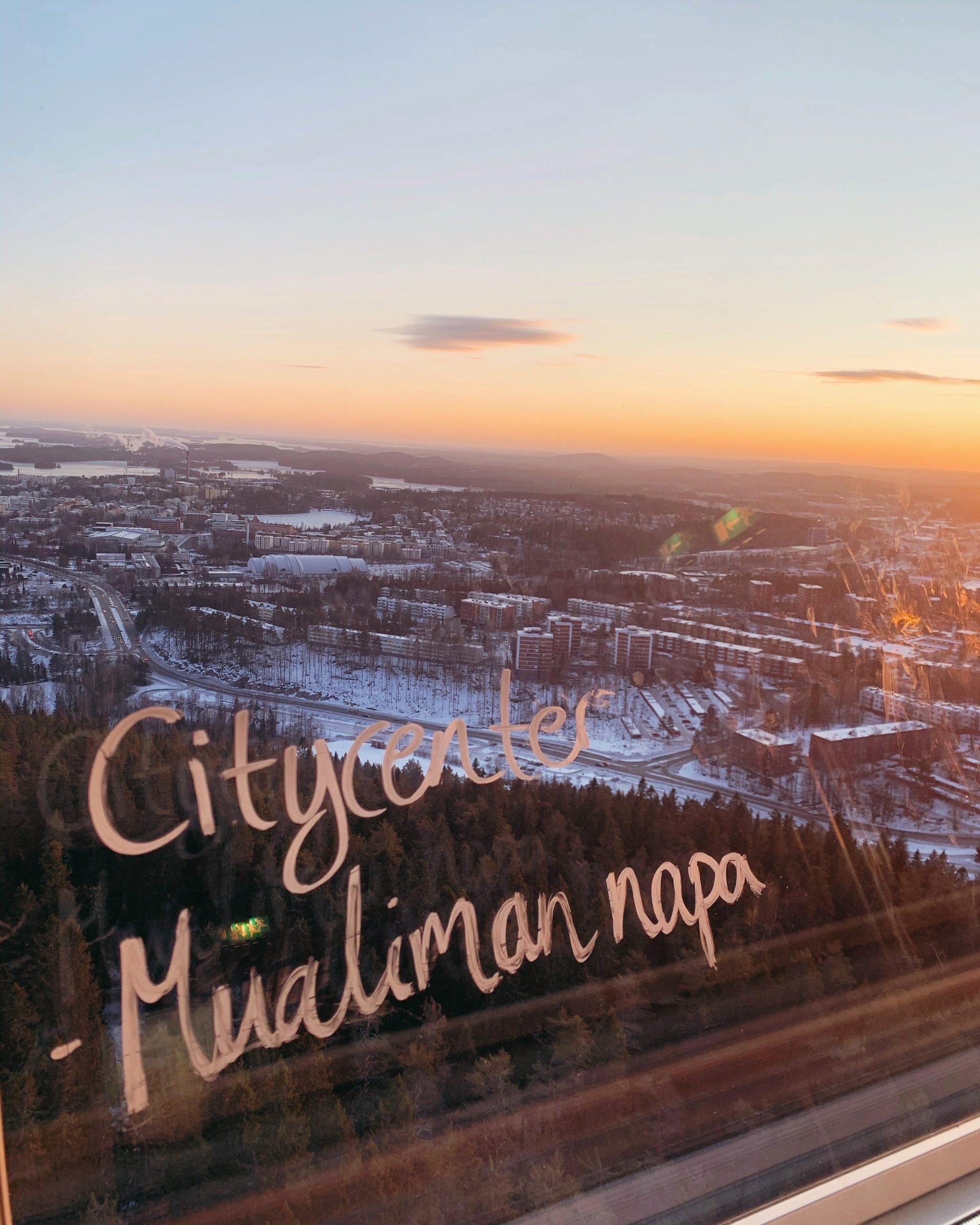 Kuopion Puijon tornista otettu kuva, lasissa teksti: Citycenter - Mualiman napa
