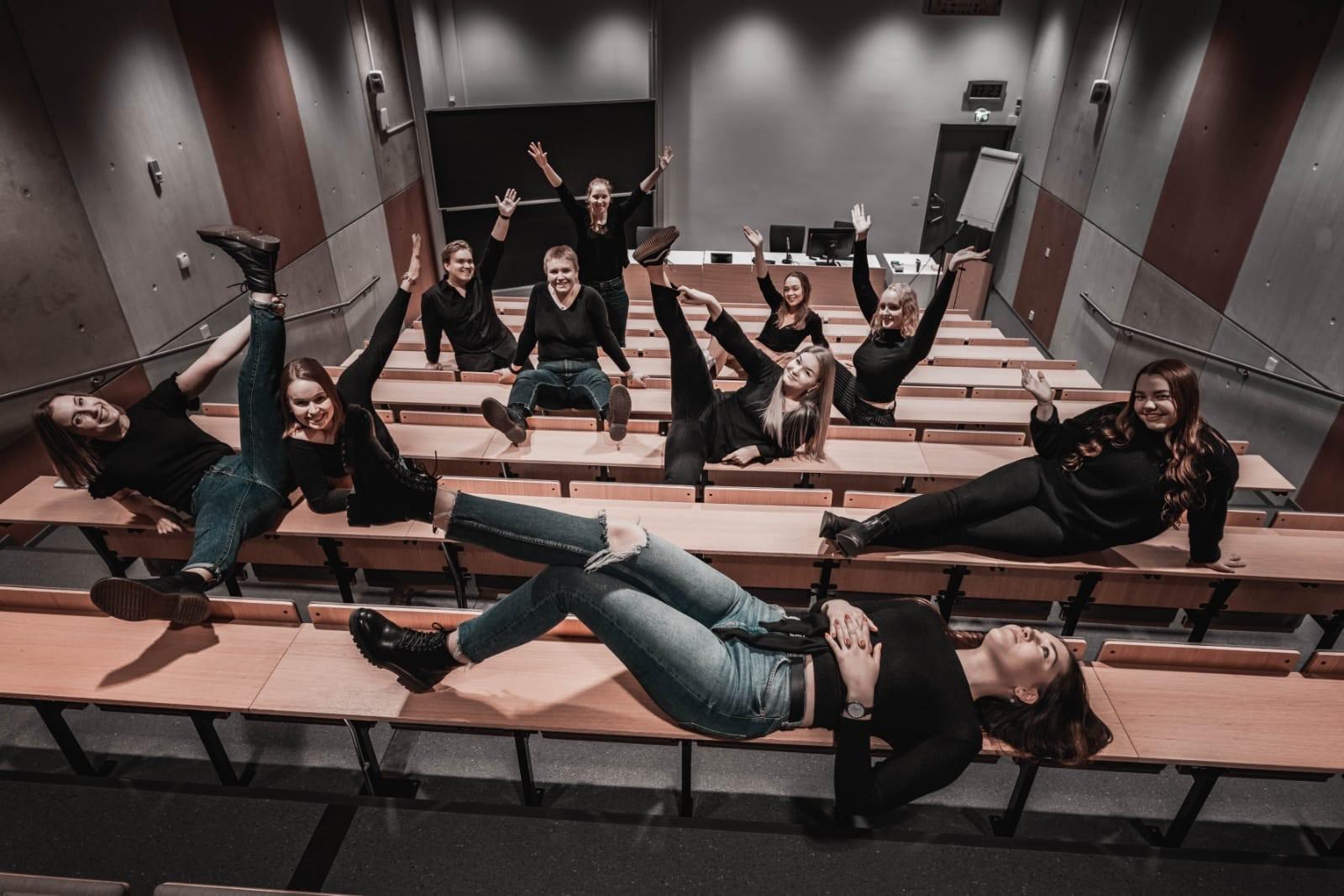 Kuva Tombolo ry:n hallituksen jäsenistä vuonna 2020 luentosalin pöydillä istumassa ja makaamassa