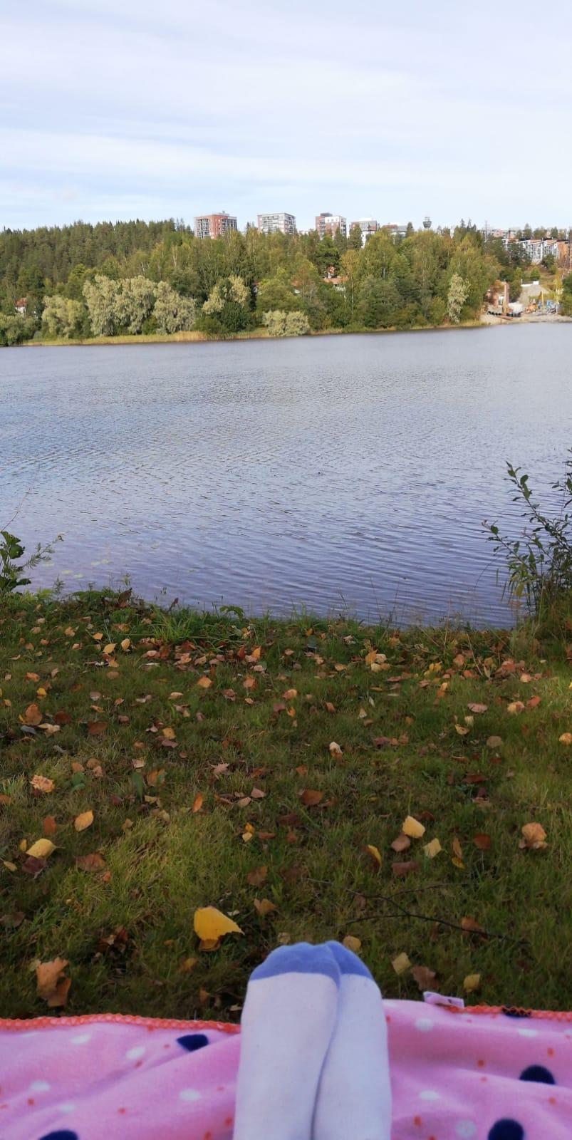 Yliopiston rantaa syksyllä, kuvassa piknikhuopa ja jalat