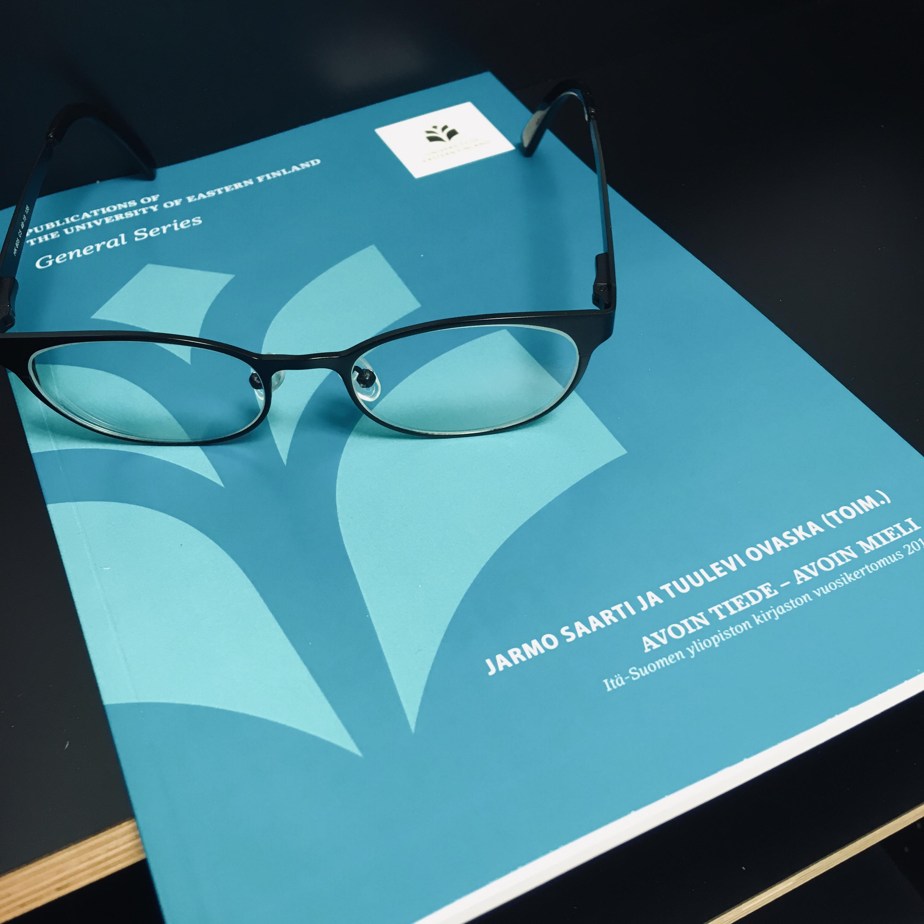 painettu vuosikertomus ja silmälasit