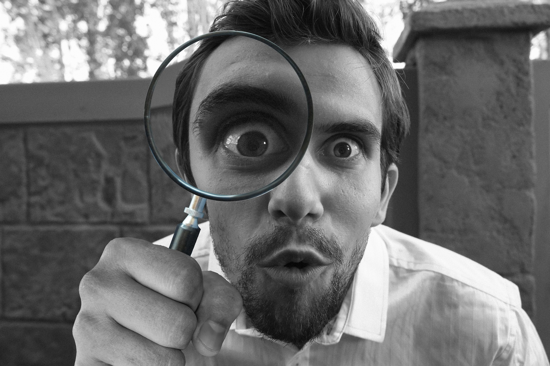 Mies katsoo suurennuslasin läpi. Man looks through a magnifying glass.