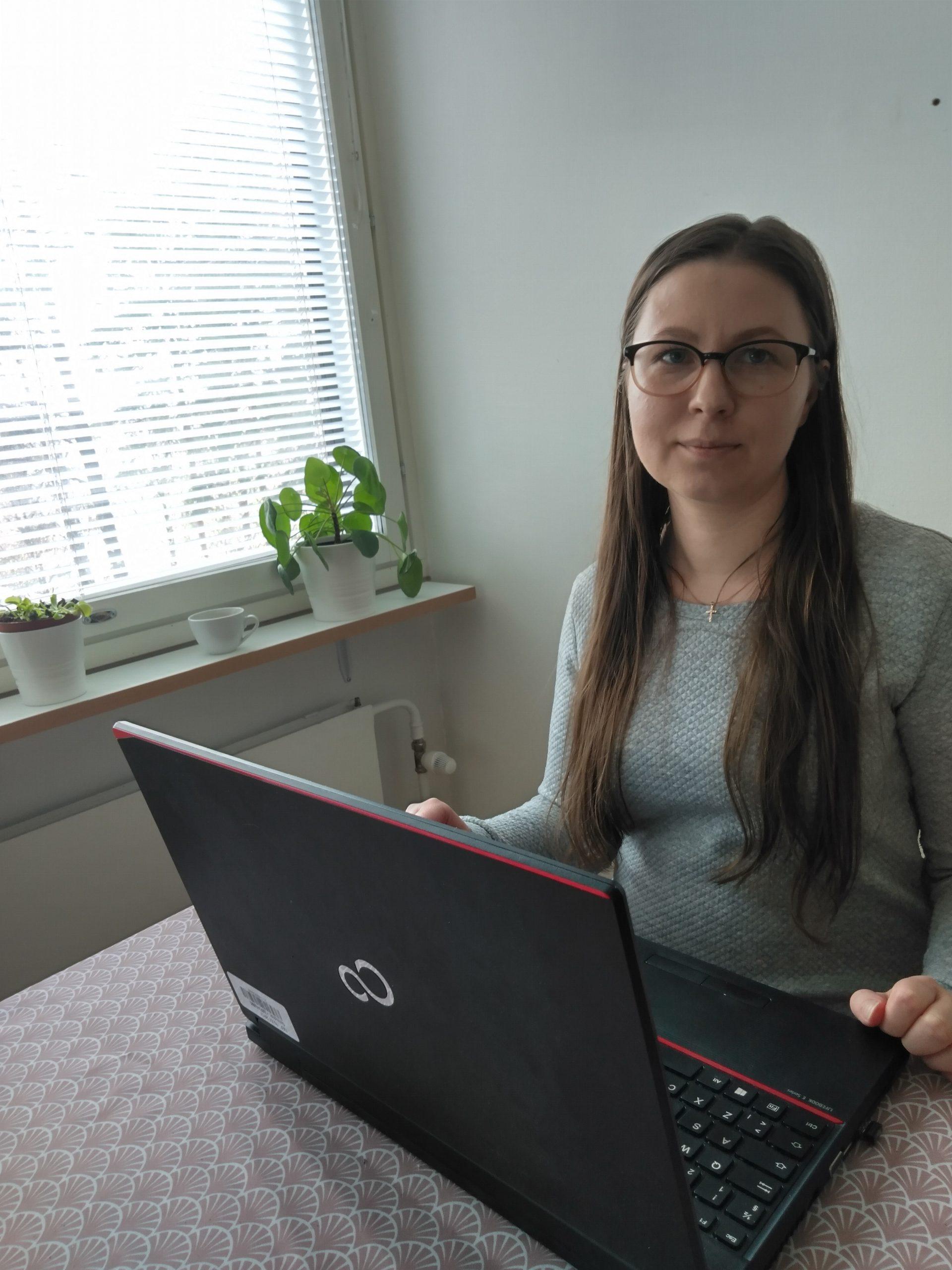 Tietopalveluneuvoja tekee etätöitä. Nainen pöydän ääressä, pöydällä kannettava tietokone, taustalla ikkuna, ikkunalaudalla viherkasveja. Woman with a laptop on a table, on the background window, plants on the windowsill.