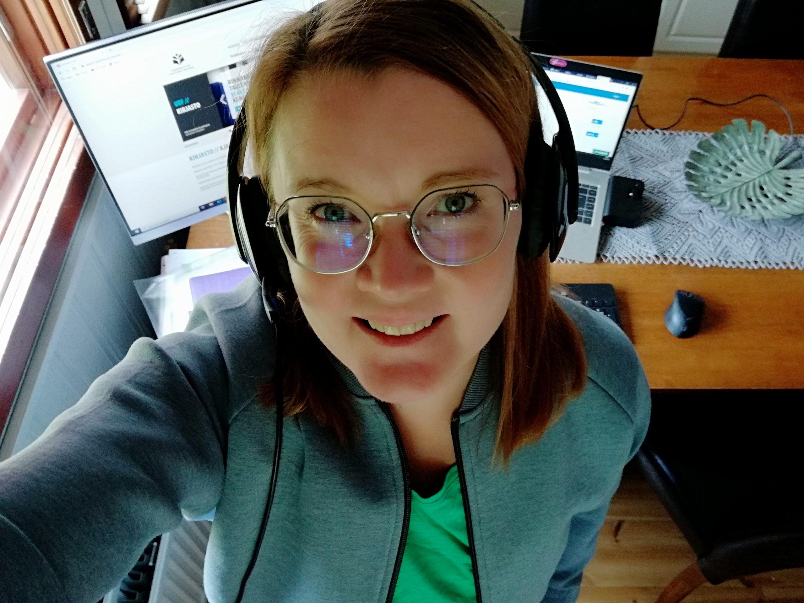 Silmälasipäinen nainen katsoo ylöspäin kohti kuvaajaa, taustalla etätyöpiste tietokoneineen.