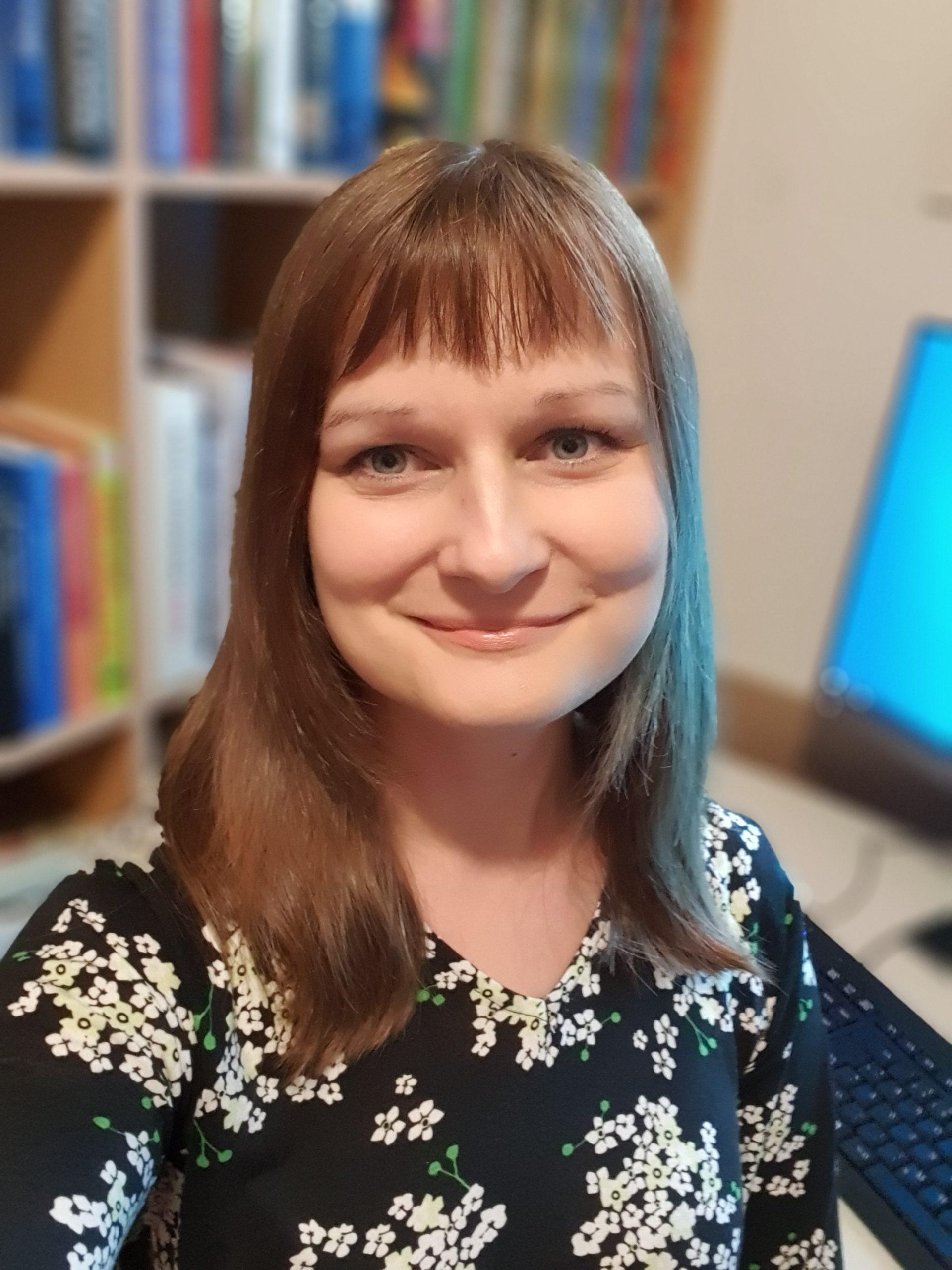 Marika hymyilee etätöissä kotitoimistossa, jossa on kirjahylly ja tietokone. Marika smiling in her office at home with bookshelf and laptop at the background.