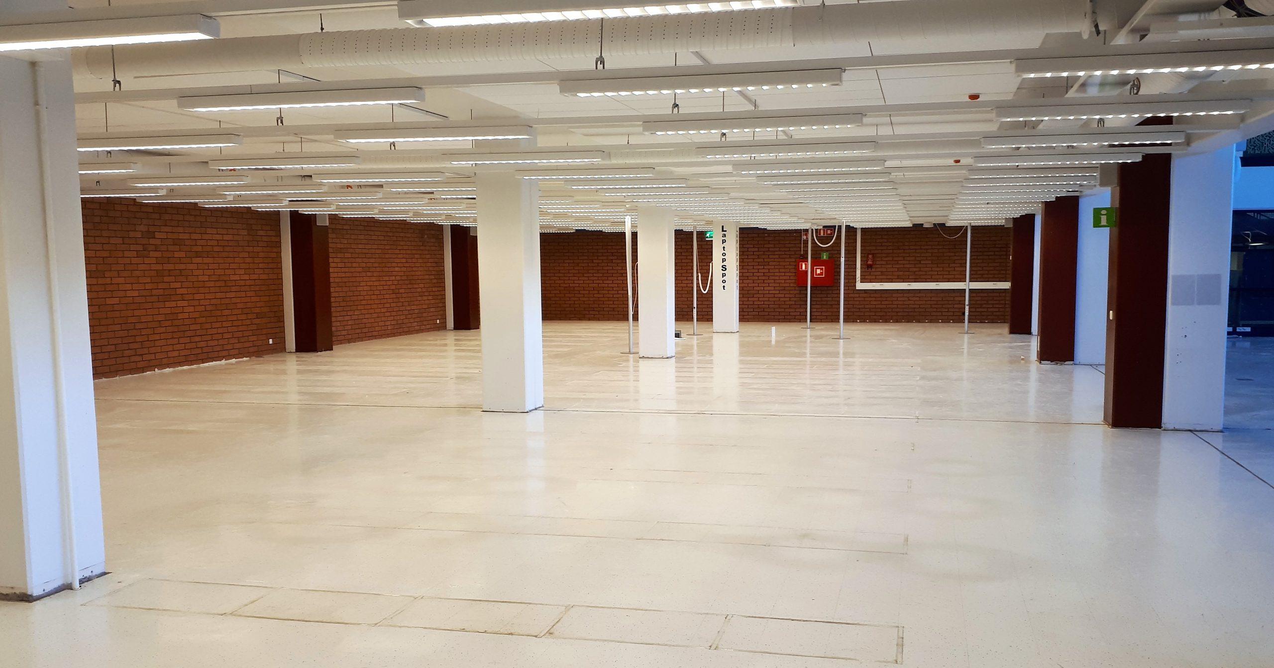 Tyhjä kirjastotila, tiiliseinä, pylväitä, nurhuinen lattia.