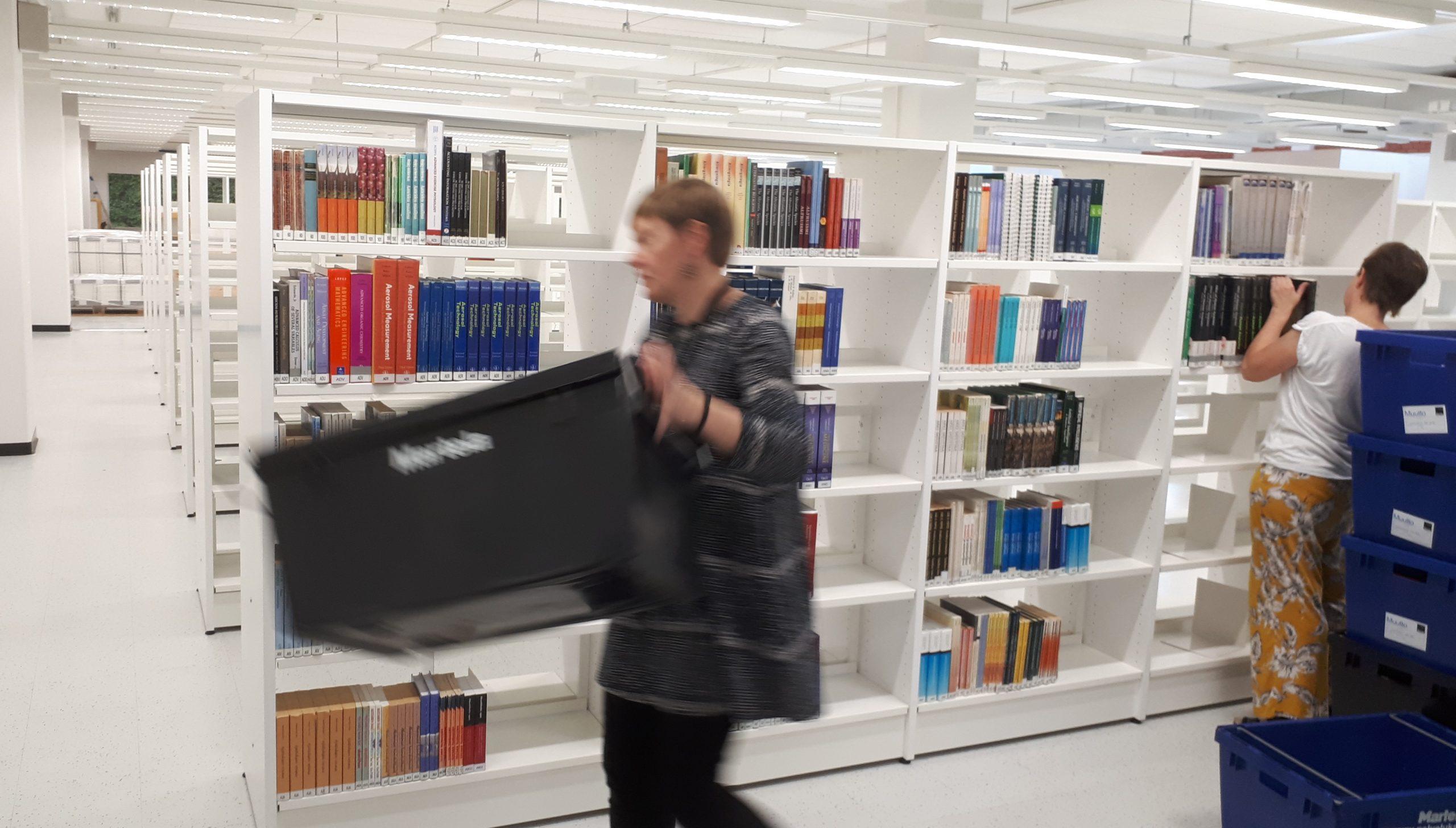 Henkilö kantaa tyhjää muovilaatikkoa. | Toinen henkilö hyllyttää kirjoja.