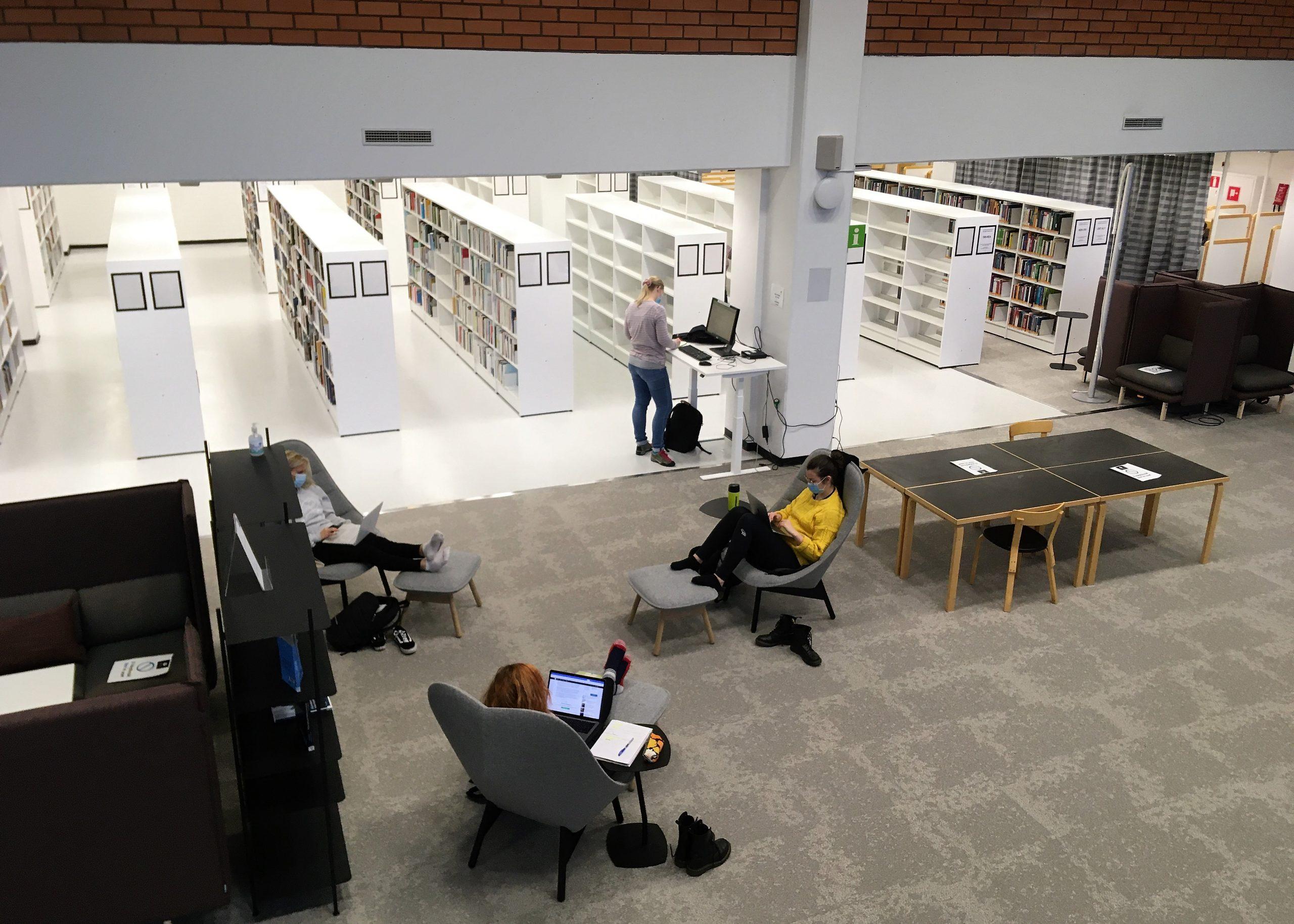 Ihmisiä lukemassa kirjastossa.