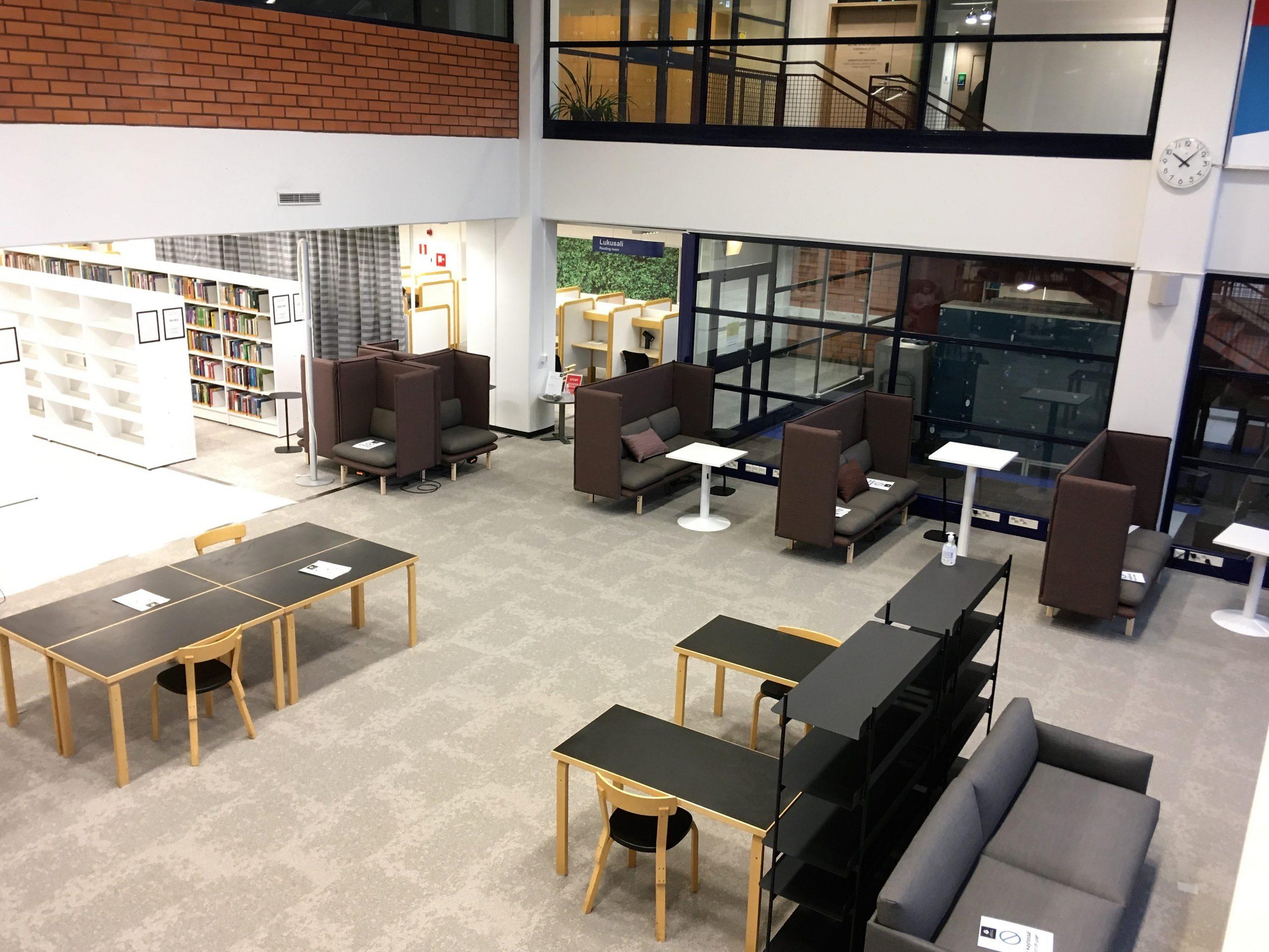 Hyllyjä, pöytiä, tuoleja kirjastossa.