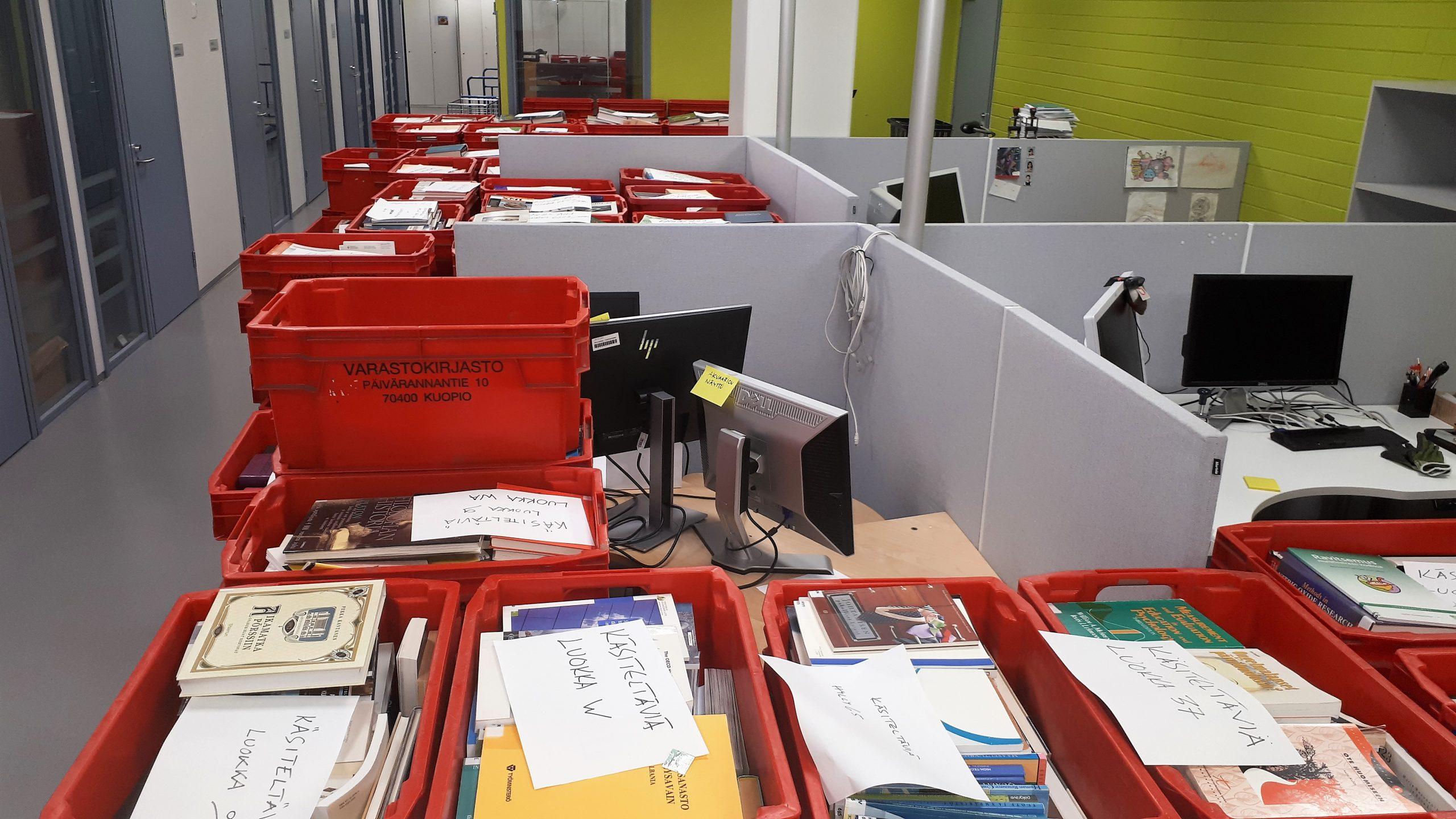 Kirjalaatikoita avokonttorin työpisteissä.