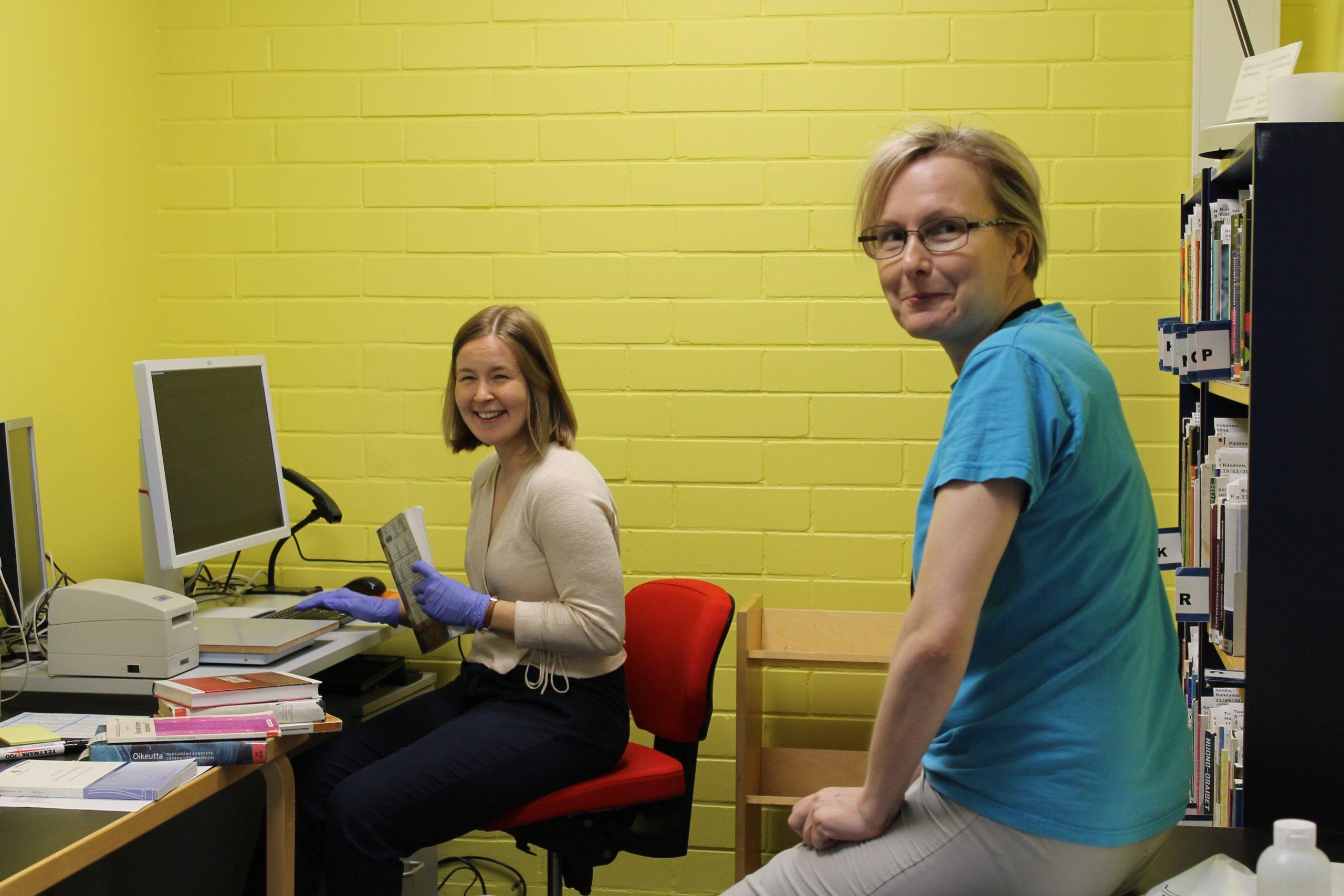 Kaksi naista - toineen tietokoneen ääressä kirja kädessä, toinen hänen takanaan, kameraan huoneessa, jossa on keltainen tiiliseinä ja musta kirjahylly täynnä kirjoja.