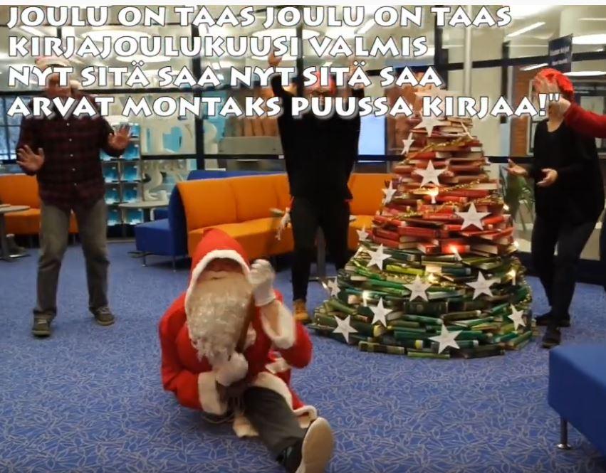 Kirjajoulukuusi, jonka edessä joulupukki soittaa kitaraa spagaatissa, taustalla kolme tonttua.