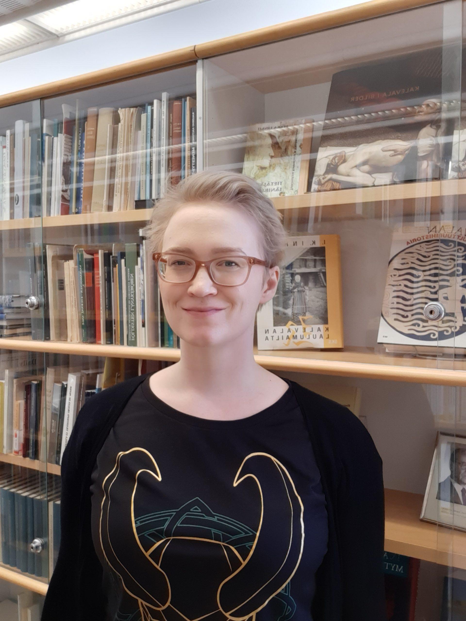 Hanna kirjahyllyn edessä. Hanna in front of a book shelf.