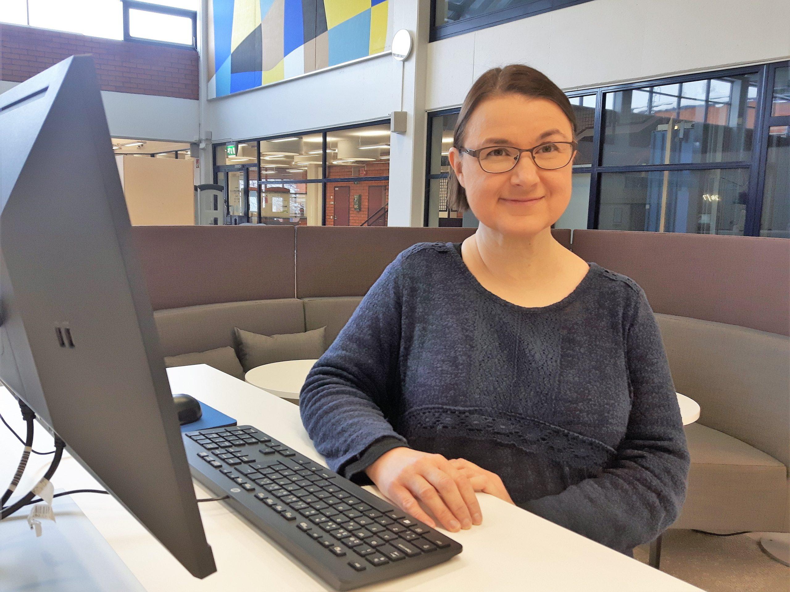 Kirjastossa Katri Rintamäki istuu tietokoneen ääressä, taustalla sohvaryhmä. Katri Rintamäki sitting by a computer, sofas at the background, library interior..
