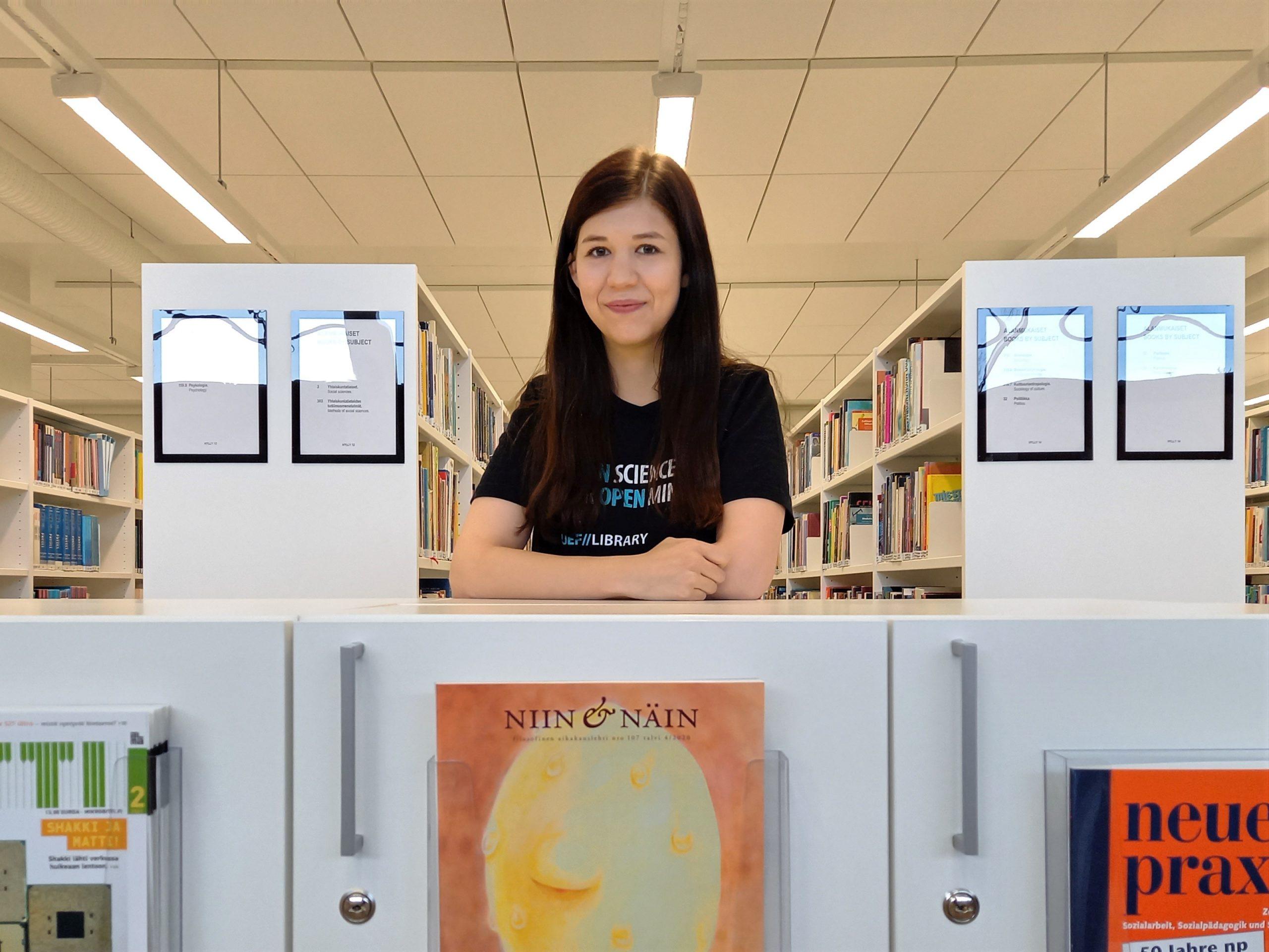 Kirjahyllyjä, lehtiä, Marjut yllään kirjaston t-paita. Book shelves, journals, Marjut wearning library t-shirt.