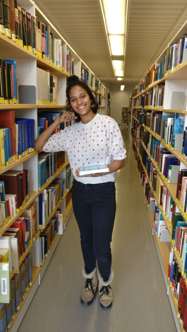 Young woman standing between bookshelves in a library.