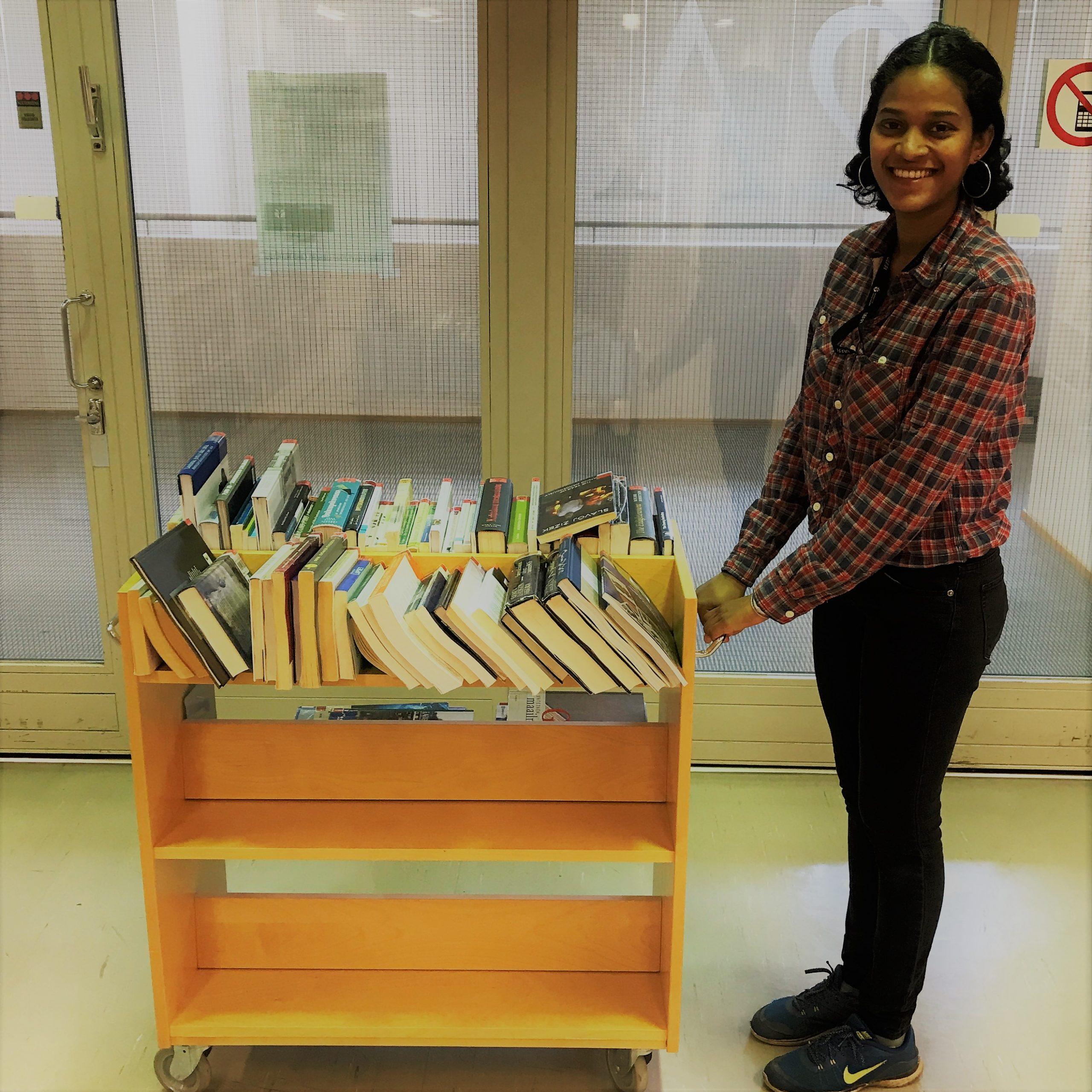Kirjakärry jossa kirjoja, nuori nainen. Book trolley and a young woman.