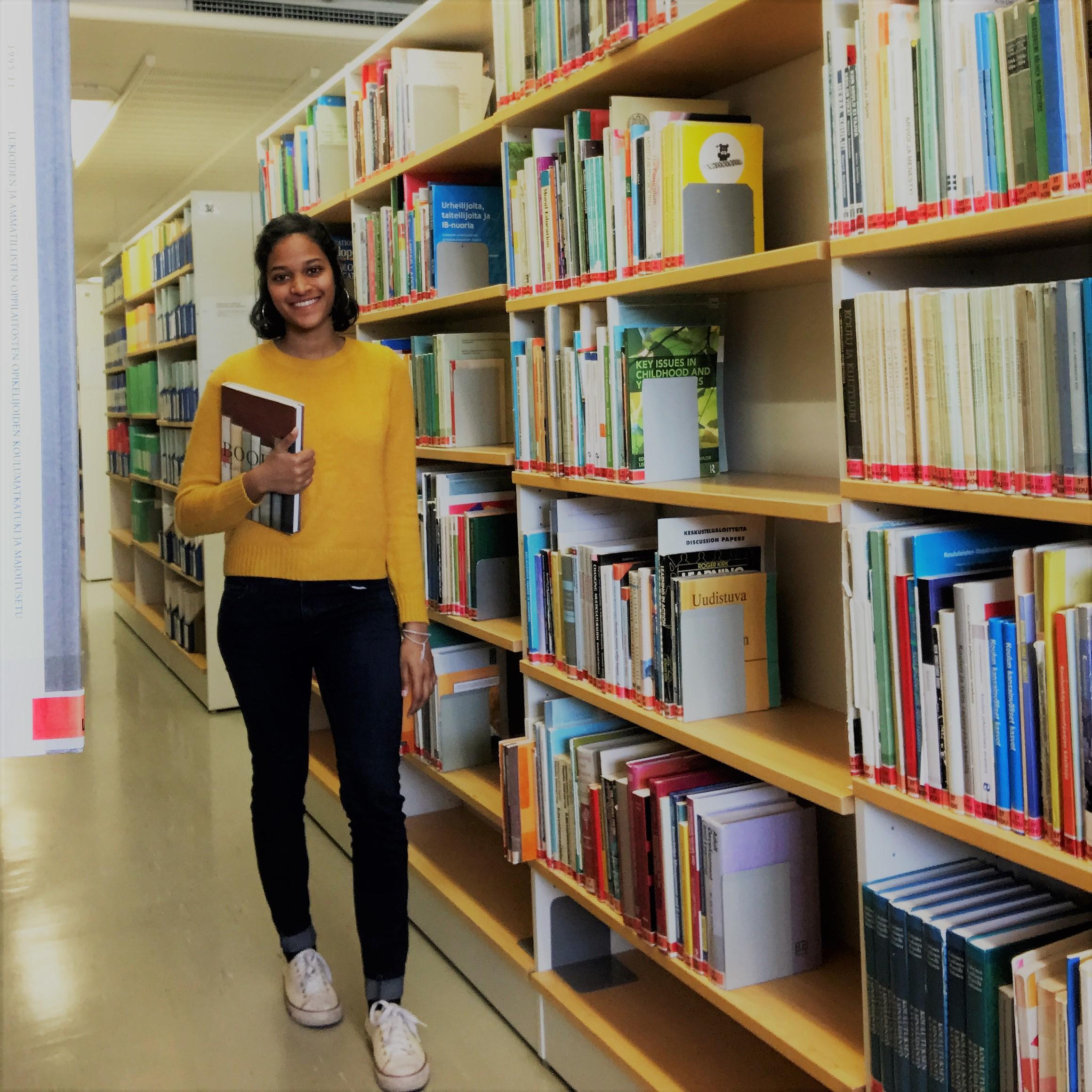 Nainen, kirjahylly, kirjoja. Woman, bookshelf, books.