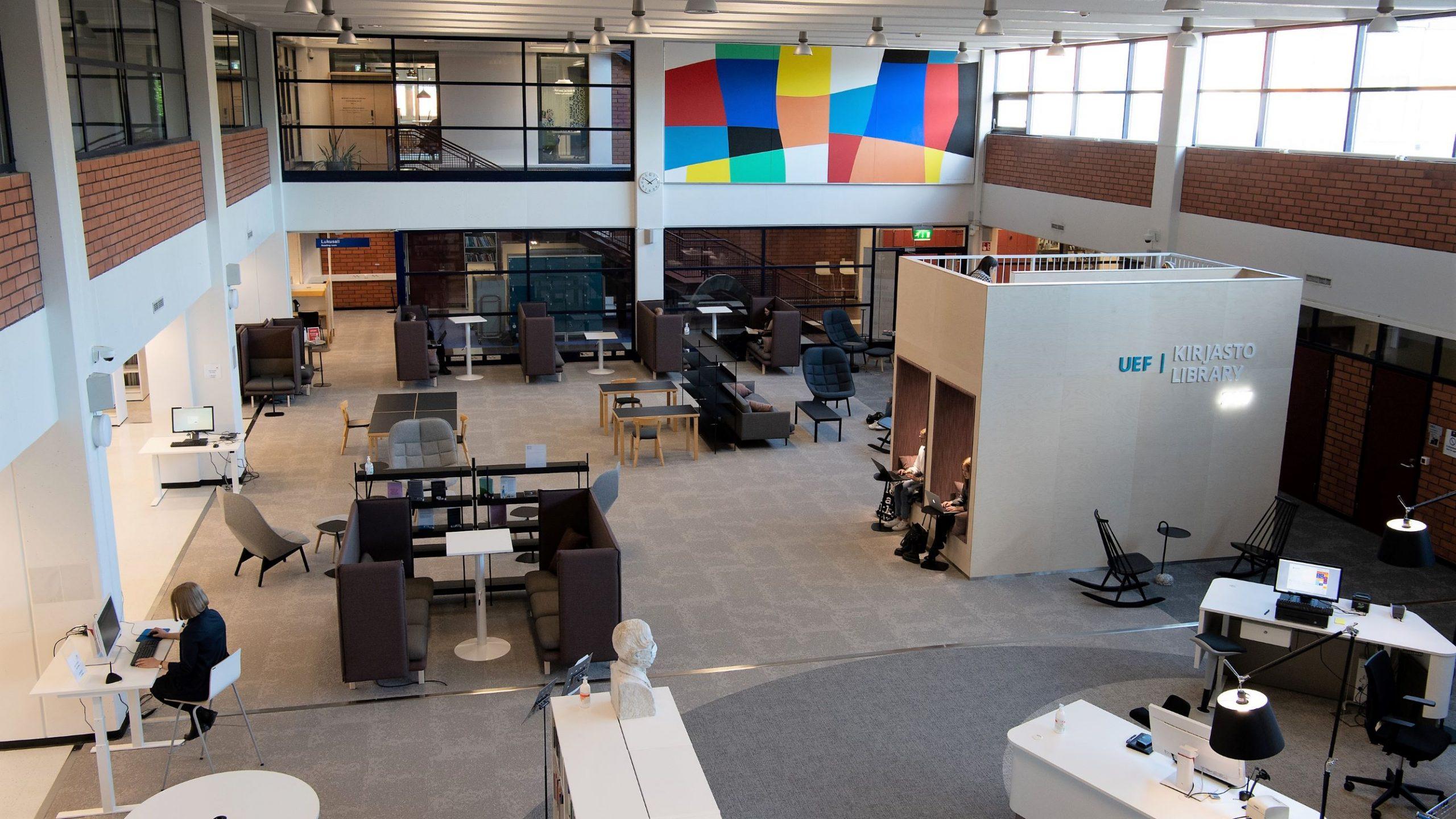 Kirjasto kuvattuna yläviistosta. Huonekaluja, lattiaa, seiniä, taidetta, ihmisiä. Library seen from above: furniture, floor, walls, art, people.