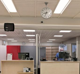 Joensuun kampuskirjaston asiakaspalvelutiski. Katto, kello, pöytä, hylly, ihminen.