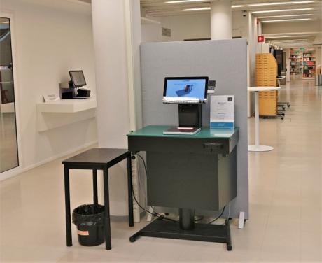 Joensuun kamouskirjaston palautus- ja lainausautomaatit. Pöytiä, sermejä, automaatteja.