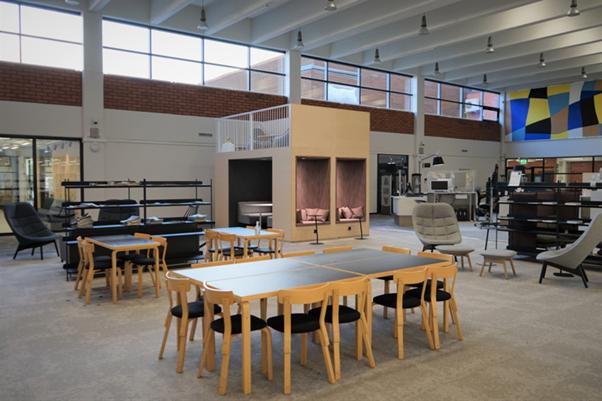 Kuopion kampuskirjaston työskentelytiloja. Parvi, seinä, erilaisia tuoleja, pöytiä, hyllyjä.