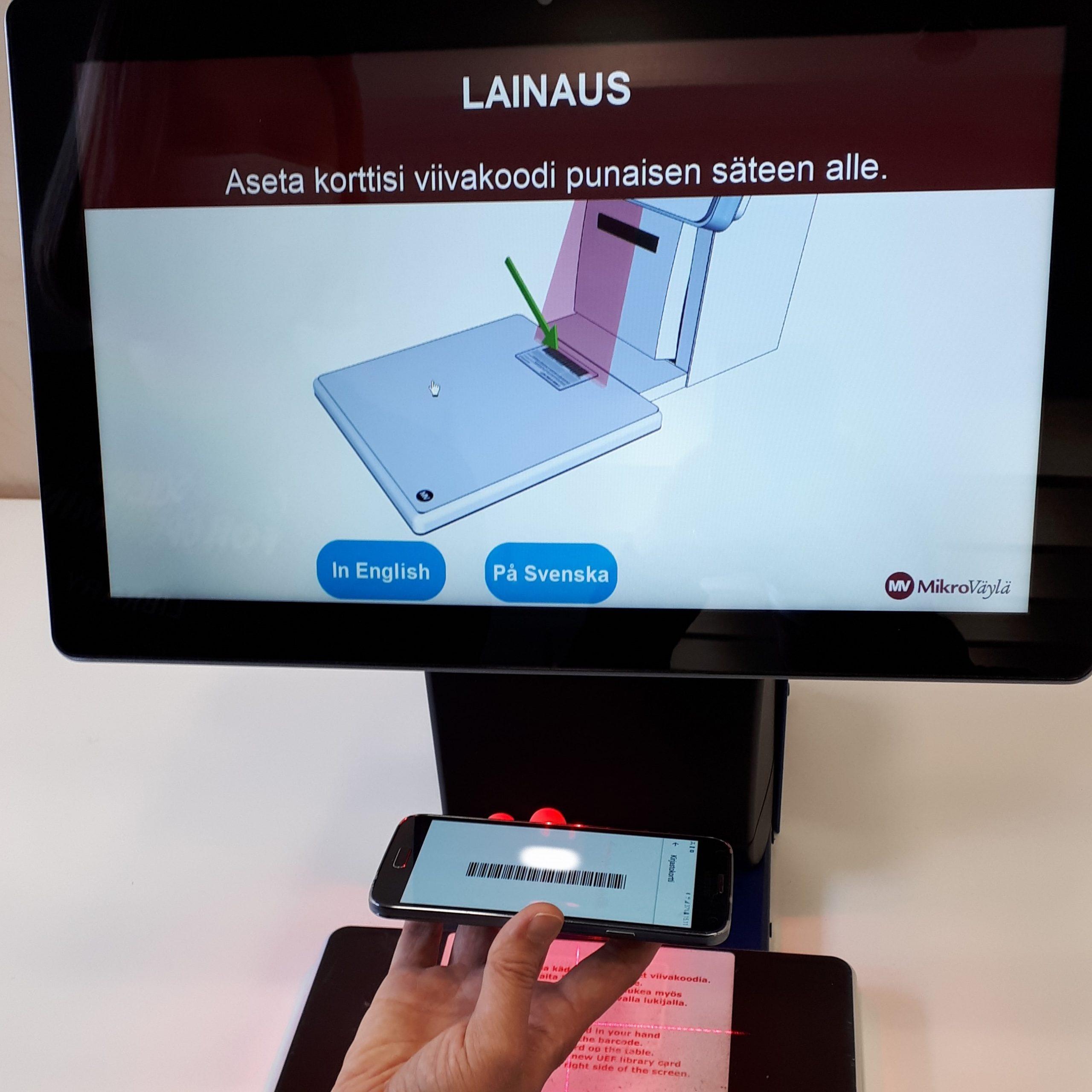Tuudo-kirjastokortti käytössä lainausautomaatilla. Näyttö, puhelin, käsi.