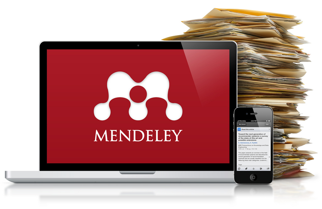 Decorative image. Laptop with Mendeley logo on the screen, mobile phone and a pile of folders.